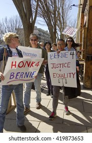 Asheville, North Carolina, USA - February 28, 2016:  An enthusiastic and diverse crowd of Bernie Sanders supporters march down an Asheville street holding signs during a political rally