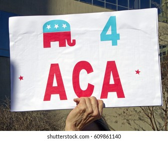 Asheville, North Carolina, USA - February 25, 2017: Close up of a hand holding a colorful sign at an Obamacare rally that shows the GOP (a Republican) symbol being for the Affordable Care Act