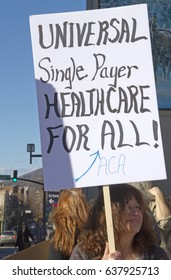 """Asheville, North Carolina, USA - February 25, 2017: Woman holds a sign saying """"Universal Single Payer Healthcare For ALL"""" at an Obamacare (Affordable Care Act) rally"""