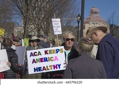 """Asheville, North Carolina, USA - February 25, 2017:  A woman holds a sign at a crowded Affordable Care Act demonstration that says """"The ACA Keeps America Healthy."""""""