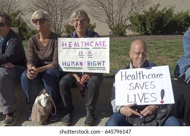 "Asheville, North Carolina, USA - February 25, 2017:  Older Americans hold signs at an Affordable Care Act rally saying ""Healthcare is a Human Right"" and Healthcare Saves Lives."""