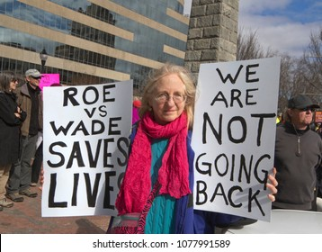 ASHEVILLE, NORTH CAROLINA, USA - JANUARY 20, 2018: An older white woman in the 2018 Women's March holds signs saying abortion saves lives and that women are not going back to when it was illegal