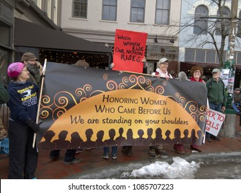 "ASHEVILLE, NORTH CAROLINA, USA - JANUARY 20, 2018: Women participating in the 2018 Women's March hold signs honoring women who came before and saying ""When women rise, our nation rises"""