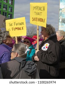 """ASHEVILLE, NORTH CAROLINA, USA - JANUARY 20, 2018: Women participating in the 2018 Women's March hold political signs saying """"The Future is Female"""" and to """"Impeach that Shithole"""" in Asheville, NC"""