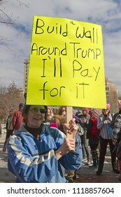 """ASHEVILLE, NORTH CAROLINA, USA - JANUARY 20, 2018: A woman  in the 2018 Women's March holds a sign saying """"Build a Wall Around Trump, I'll Pay For It"""" in reference to the Mexican border wall he wants"""