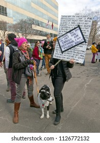 "Asheville, North Carolina, USA – January 20, 2018: Angry woman, hold a large sign filled with grievances about Donald Trump with a sign pasted over it saying ""Because this sign is not big enough for e"