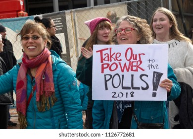 "Asheville, North Carolina, USA – January 20, 2018: Woman banding together at the American 2018 Women's March with a sign that says ""Take Our Power to the Polls, 2018!"" in downtown Asheville, NC"