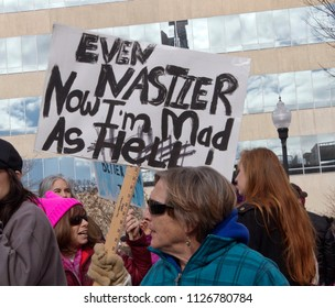 "Asheville, North Carolina, USA – January 20, 2018: A woman marching in the 2018 Women's March holds a sign saying ""Even nastier now I'm mad as Hell!"" The 2018 Women's March in downtown Asheville, NC"