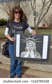ASHEVILLE, NORTH CAROLINA, USA – JANUARY 20, 2018: A woman in the 2018 Women's March holds a sign showing the Statue of Liberty with her head on her hands despairing for American freedom and values, o