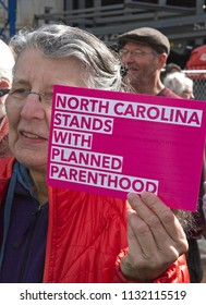 "Asheville, North Carolina, USA – January 20, 2018: An older female demonstrator in the American 2018 Women's March holds a colorful sign that says ""NORTH CAROLINA STANDS WITH PLANNED PARENTHOOD"""