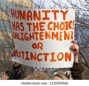 "ASHEVILLE, NORTH CAROLINA, USA - JANUARY 20, 2018: Woman in the 2018 Women's March holds a sign saying ""Humanity Has the Choice, Enlightenment or Extinction"""