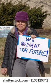 "ASHEVILLE, NORTH CAROLINA, USA - JANUARY 20, 2018: A woman holds a sign at the 2018 Women's March that says ""Let's Reinvent Our Future!"" with an ""Altitude Affects Attitude"" sign in the background"