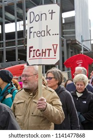 """ASHEVILLE, NORTH CAROLINA, USA - JANUARY 20, 2018: Man walking in the 2018 Women's March holds a political sign saying """"Don't Freak...Fight!"""""""