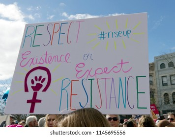 "Asheville, North Carolina, USA – January 20, 2018: A young woman marching in the 2018 Women's March holds a political, gender related sign saying ""Respect My Existence or Expect My Resistance"""