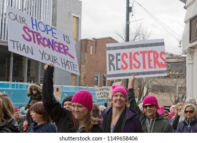 "Asheville, North Carolina, USA – January 20, 2018: Young women in pussyhats march in the 2018 Women's March holding political signs saying ""Resisters"" and ""Our Hope is Stronger Than Your Hate"""