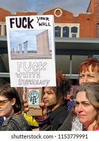 "Asheville, North Carolina, USA – January 20, 2018: A woman among a crowd marching in the 2018 Women's March holds a political sign that says ""Fuck Your Wall"" and ""Fuck White Supremacy"""