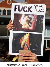 "Asheville, North Carolina, USA – January 20, 2018: A woman marching in the 2018 Women's March holds a sign showing Nazi and Confedeate flags burning that says ""Fuck Your Flags"""