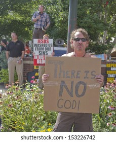 ASHEVILLE, NORTH CAROLINA, USA - JULY 26: Men hold opposing religious and Atheist signs at the Bele Chere Festival on July 26, 2013 in Asheville, North Carolina