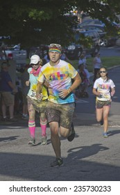 Asheville, North Carolina, USA - July 26, 2014:  Runners splattered with colorful dyes race in the the happy Asheville 5K Color Run on July 26, 2014 in downtown Asheville, NC