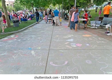 ASHEVILLE, NORTH CAROLINA, USA - JUNE 9, 2017: Children's chalk artwork line the wide sidewalk of Pack Square as families gather for a summer outdoor event in downtown Ashevile, NC