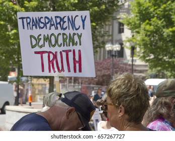 "Asheville, North Carolina, USA - June 3, 2017: Close up of an American flag and political sign at a ""March For Truth"" rally saying ""Transparency, Democracy, Truth"""