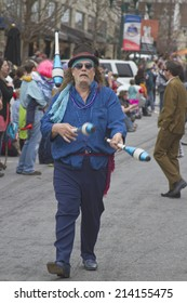 Asheville, North Carolina, USA - March 2, 2014:  A juggler juggles pins in Mardi Gras Parade on March 2, 2014 in downtown Asheville, NC