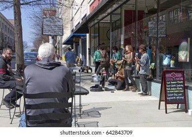 Asheville, North Carolina, USA - March 24, 2017:  People sit at tables on the street by buskers playing for tips in front of the historic Woolworth Building and a man doing push ups on the sidewalk