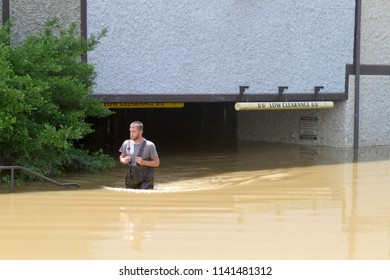 ASHEVILLE, NORTH CAROLINA, USA - MAY 30, 2018: A young man wades through hip high muddy water as he walks out from a flooded low level parking garage into the sunlight in Asheville, NC
