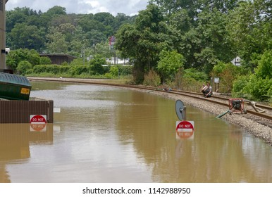 ASHEVILLE, NORTH CAROLINA, USA - MAY 30, 2018: Men wait while flood water pumps drain a deeply flooded apartment parking lot after heavy rains, pumping it into a ditch by the railroad tracks