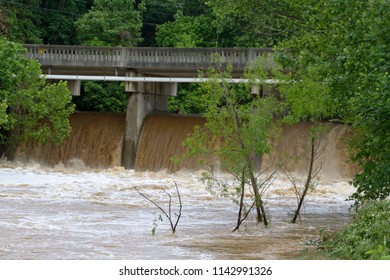 ASHEVILLE, NORTH CAROLINA, USA - MAY 30, 2018: A dam releasing the wildly turbulent, muddy water of a flooding river after days of rain in western North Carolina