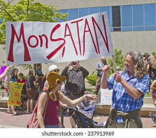 "Asheville, North Carolina, USA - May 25, 2013: Genetically modified food protesters hold up a sign calling Monsanto ""MonSATAN""at a GMO protest rally on May 25, 2013 in downtown Asheville, NC"