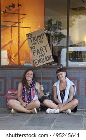 """Asheville, North Carolina, USA: September 12, 2016: Two young women hold a sign at a Donald Trump campaign rally saying  """"To Trump Means to Fart in England"""" on September 12, 2016 in Asheville, NC"""