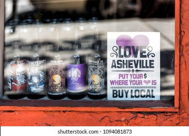 Asheville, USA - April 19, 2018: Downtown old town street in hipster North Carolina NC famous town, city with storefront store, shop, nobody display of local beer, sign