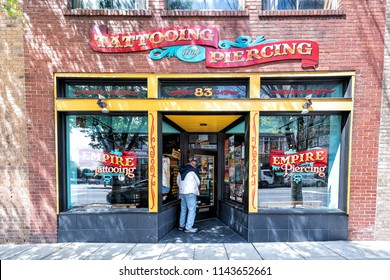 Asheville, USA - April 19, 2018: Empire Tattoo tattooing and piercing store, shop, storefront, people, man entering through door in downtown on Patton Avenue