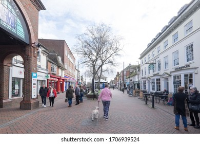 Ashford, Kent, United Kingdom - March 9, 2020: People walking and chatting on High Street in the pedestrianised town centre with shops