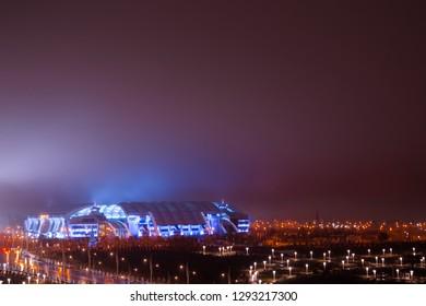 "Ashgabat, Turkmenistan. 18 December 2018. City at night. Illuminated Stadium ""Ashgabat"" on a background of beautiful violet skyline."