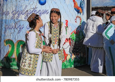 ASHGABAT, TURKMENISTAN -  January, 04, 2017: Two unknown young girls in national clothes laugh and talk. ASHGABAT, TURKMENISTAN -  January, 04, 2017
