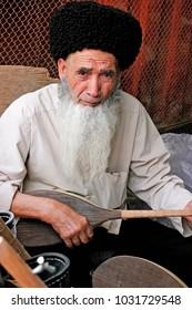 Ashgabat, Turkmenistan - March 09, 2013.  Portrait of Turkmen man in telpek with bushy beard. Oriental bazaar. Ashgabat, Turkmenistan - March 09. 2013.