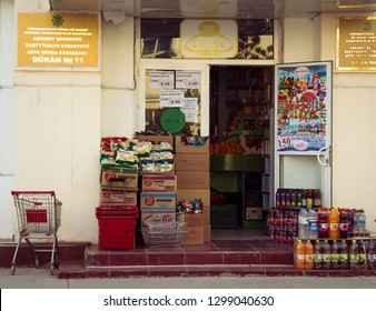 """Ashgabat,Turkmenistan. 26 January 2019. Local minimarket (Dukan) """"Desse"""". Entrance with open door to a shop. Newly delivered merchandise outdoors to be sorted on a shelves of a shop by a sales people."""