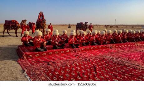 Ashgabat/Turkmenistan-January 25, 2018: Turkmenistan men. Turkmenistan men sitting on the carpet playing national musical instruments. desert. red carpet