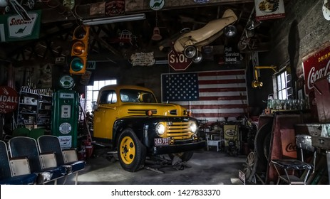 Ashgrove, MO/USA - June 5: 2018: Yellow Vintage Pickup Truck With Headlights In Old Garage With Memorabilia And American Flag In Background On Historic Route 66.