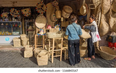 Ashila Morocco; June 14, 2018: Tourists buying handmade baskets and traditional Berber hats in a market of Morocco