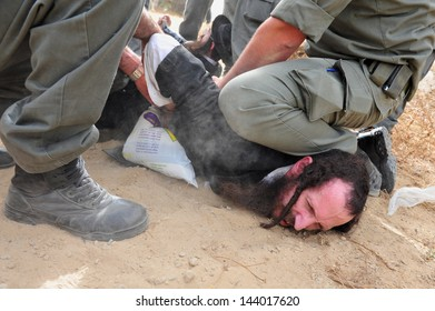 ASHKELON, ISR - MAY 16:Israeli police forces aressting Jewish orthodox man during protest on May 16 2010. It's Israel Police special patrol unit dedicated for crowd control and special operations.