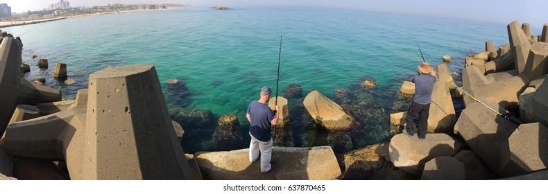 Ashkelon - Israel, April 2017: panoramic view of two fishermen fishing at the Mediterranean Sea