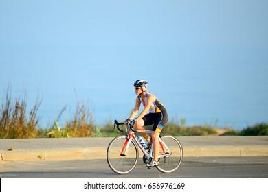 ASHKELON, ISRAEL- JUNE 09, 2017: Israeli elderly woman rides a bicycle along Ashkelon beach.