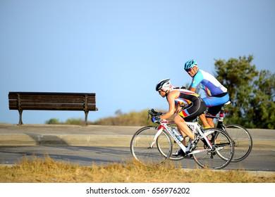 ASHKELON, ISRAEL- JUNE 09, 2017: Israeli adult man and woman ride a bicycle along Ashkelon beach.