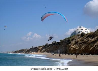 ASHKELON, ISRAEL - OCTOBER 04, 2017: ASHKELON, ISRAEL - OCTOBER 04, 2017: Motoparaplane flies over the beach in Ashkelon on the Mediterranean Sea