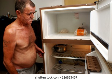 ASHKELON - JULY 30:A poor man looking into his empty food refrigerator in his home in Ashkelon, Israel.About 20.5% of Israeli families living below the poverty line.