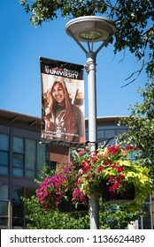 ASHLAND, OREGON/U.S.A. - JUNE 23, 2018: A photo of a Southern Oregon University banner on the college campus with summertime flower pots.