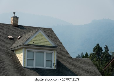 ASHLAND, OR/U.S.A. - AUGUST 19, 2017: A photo of the roof of a house in town with smoke from summer wildfires clouding the mountains behind it.
